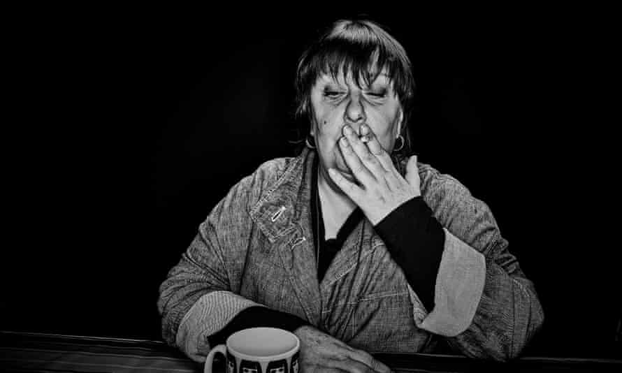 Kathy Burke sitting at a table in her house, smoking a cigarette
