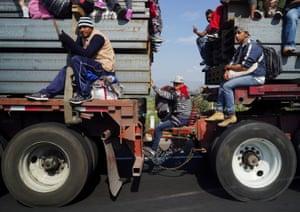 People on lorries as part of the migrant caravan in Mexico