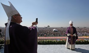 Bishops take pictures of the massed pilgrims before Pope Francis addressed the crowd.