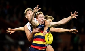 Adelaide's Tom Lynch attempts to mark the ball ahead of Sam Gilbert and Sean Dempster of St Kilda.