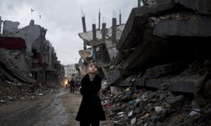 A Palestinian boy looks up during a rain storm while walking through a neighbourhood destroyed