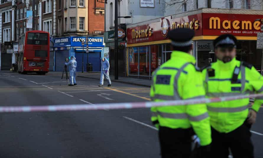 Forensic officers examine the scene of the attack on Streatham High Road, south London.