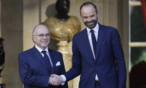 Édouard Philippe, right, is greeted by outgoing prime minister Bernard Cazeneuve in Paris