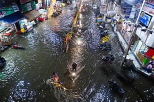Allahabad, India Commuters make their way through a flooded street after heavy rains