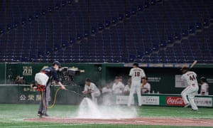 A ground staff sprays water on the pitching mound just minutes before a behind-closed-doors opening game between Yomiuri Giants and Tokyo Yakult Swallows at Tokyo Dome