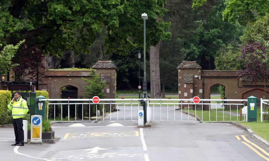 A private security guard outside the 964-acre gated community of St George's Hill in Surrey.