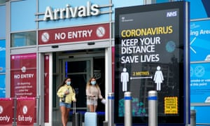 Passengers wearing protective masks leave the arrivals terminal at Birmingham airport.