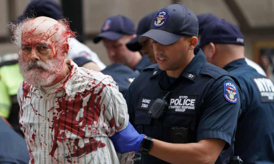A climate crisis activist covered in fake blood is arrested in New York City during the Extinction Rebellion demonstration.