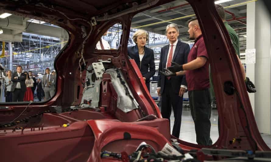 Theresa May and the chancellor, Philip Hammond, view a car production line in Solihull