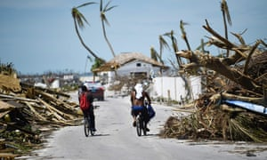 Residents pass damage caused by Hurricane Dorian in Marsh Harbour, Great Abaco Island in the Bahamas.