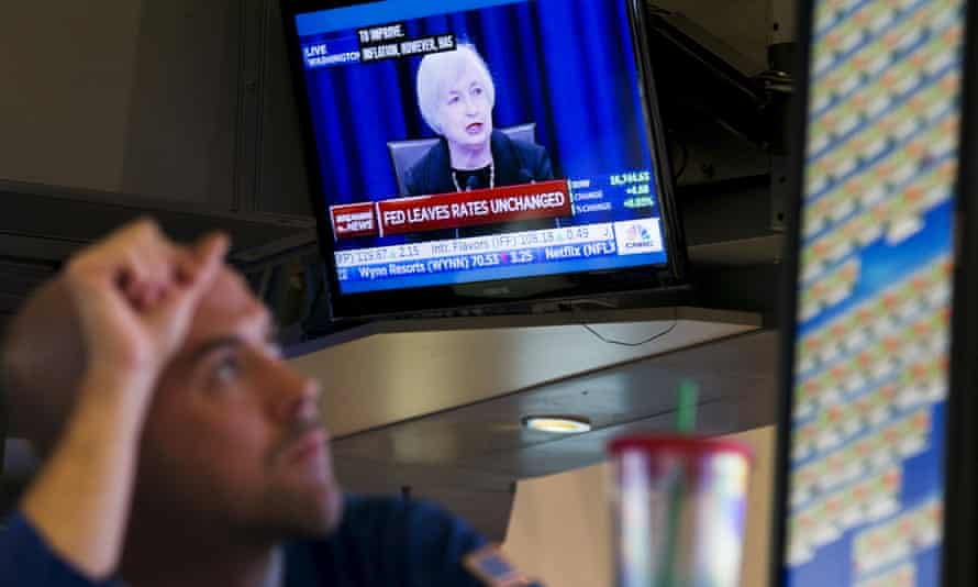 A trader works underneath a TV screen showing Janet Yellen announcing that the Federal Reserve will leave interest rates unchanged, on the floor of the New York Stock Exchange in New York on Thursday.
