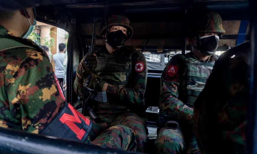 Myanmar soldiers sit inside a military truck outside a Hindu temple in Yangon on Tuesday
