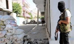 An armed Kurdish militant stands near a barricade