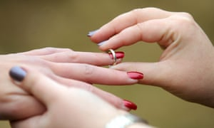 A woman places a wedding ring on her partner's finger