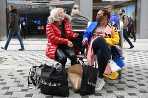 Two women sit on a bench with bags of shopping in Cardiff, Wales