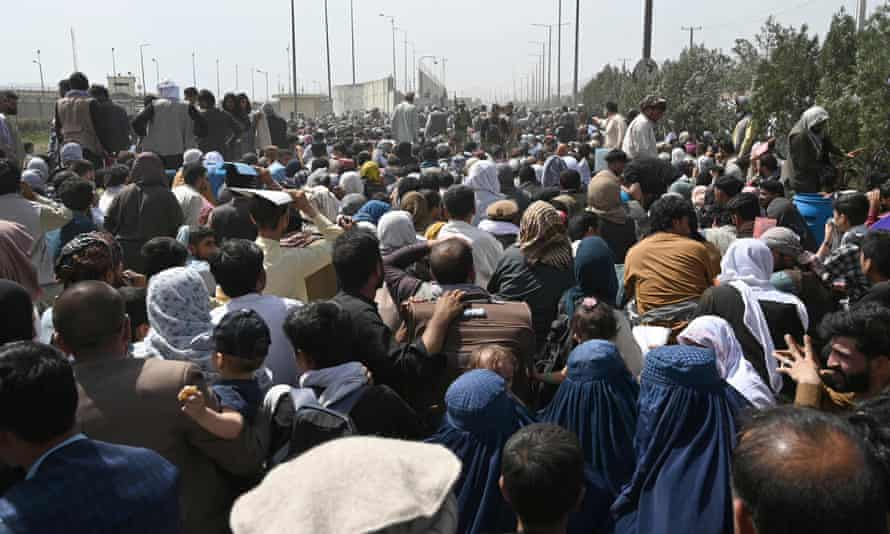 Afghans gather on a roadside near the military part of Kabul airport hoping to flee the country after the Taliban's takeover.