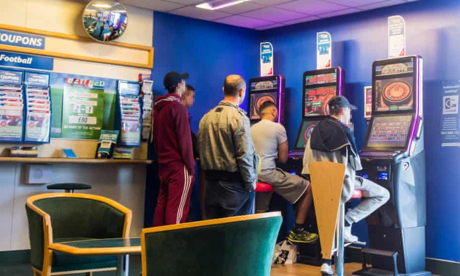 Men clustered around fixed odds gaming machines in Bet Fred Betting shop