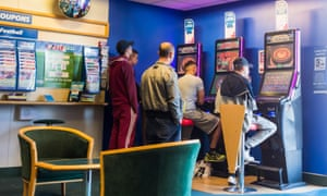 Men gather around a fixed-odds betting terminal in a betting shop