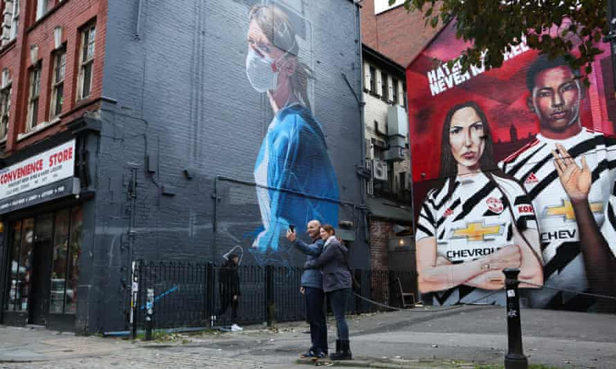 People taking photographs of a mural depicting an NHS worker wearing a face mask during the Covid-19 pandemic on October 16, 2020 in Manchester, England.