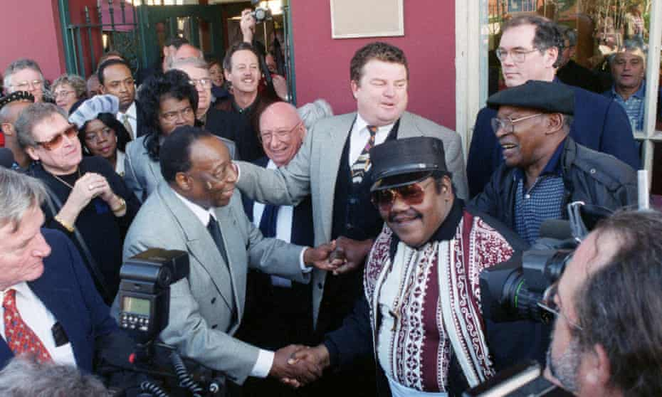 Fats Domino, center right, shakes hands with Dave Bartholomew, left, amid a crowd of former colleagues at the 50th anniversary observance of Domino's first recording session in New Orleans, December 1999.