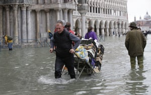 A greengrocer pulls his cart through high waters