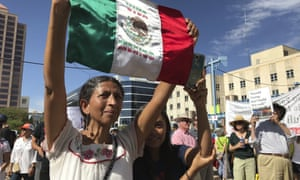 Margarita Perez of Albuquerque, with her daughter by her side, holds up a Mexican flag during a protest on Civic Plaza in Albuquerque, New Mexico, on Saturday, June 30, 2018. Perez was among thousands who gathered on the plaza to voice their opposition to US immigration policies and President Donald Trump.