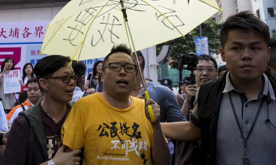 Pro-democracy activist Tam Tak-chi is moved along by police after confronting Hong Kong government supporters in April.