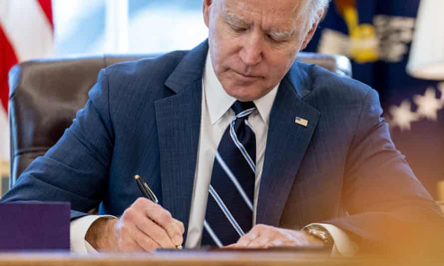 Biden signs the American Rescue Plan, a chuge oronavirus relief package, on 11 March.