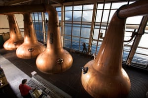The Caol Ila whisky distillery on the Isle of Islay.the still men at Caol Ila scotch whisky distillery, pause at dawn, to take in the view. The stills are of traditional shape. The tall windows of the stillroom overlook the Sound of Islay with Jura and the Paps of the Jura in the background.