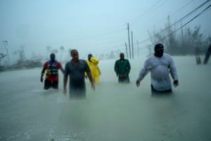 Volunteers walk under the wind and rain of Hurricane Dorian, on a flooded road after rescuing several families that arrived on small boats, near the Causarina bridge in Freeport, Grand Bahama, Bahamas.