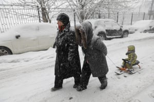 A woman pulls a child on a sledge through the snow.