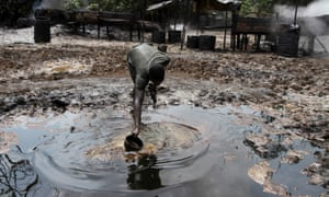 A man collects polluted water in the Niger Delta