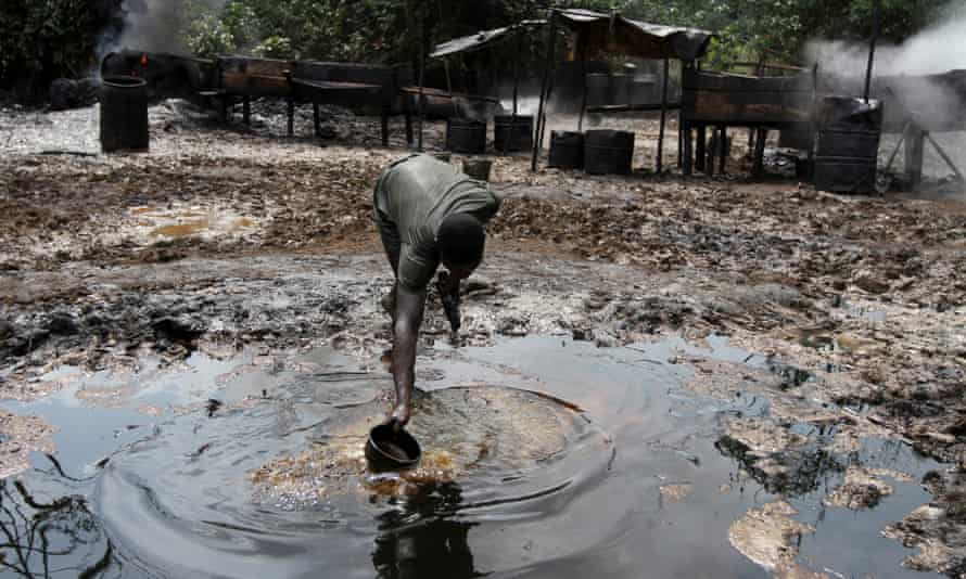 A man collects polluted water at an illegal oil refinery site in Bayelsa.