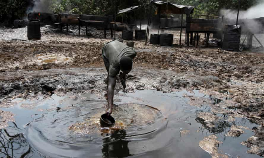 A man collecting polluted water at an illegal oil refinery site near river Nun in Bayelsa, Nigeria