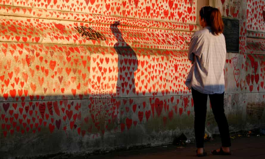 A woman looks at the memorial wall of more than 150,000 hearts, each representing a coronavirus death, in evening sunlight in London in April.