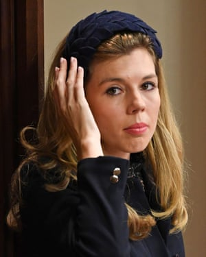 Carrie Symonds holding a hand up to her headband at the state opening of parliament