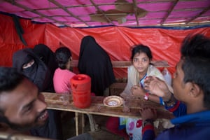 People have lunch in a makeshift cafe in the 'OO' section of the camps