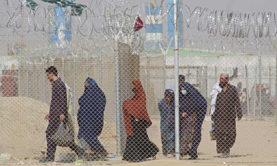 Afghans fleeing the Taliban enter Pakistan through the border crossing point in Chaman.