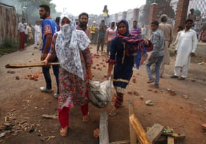 Kashmiri women girls carry a bag filled with bricks and stones to help protesters during clashes with Indian forces in in Anchar,