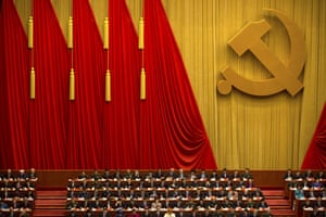Attendees read a work report during the opening session of China's 19th party congress at the Great Hall of the People in Beijing
