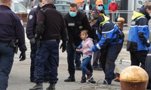 French Gendarmes and police assist migrants, including five children and a baby, who tried to reach England by crossing the Channel, and who were rescued off the French port city of Calais on 16 May 2020.