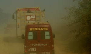 Fire trucks vehicles advance through smoke from forest fires nearPorto Velho, Rondonia.