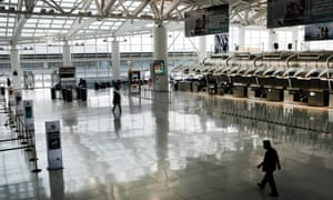 People walk through a sparse international departure terminal at John F Kennedy airport on 7 March 2020 in New York City.