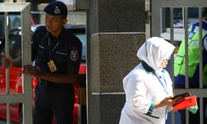A police officer looks on as a hospital staff walks past outside the morgue at Kuala Lumpur general hospital where Kim Jong-nam's body was taken after his death on Monday.