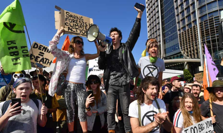 Extinction Rebellion protesters block the corner of Margaret and William streets during a climate change protest in Brisbane