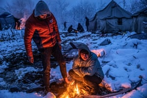 Two migrants from Afghanistan gather around the fire of a burning abandoned tent to warm up and dry their wet feet.