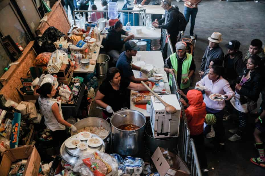Photograph taken by Ariana Drehsler of volunteers feeding lunch to migrants from Central America at a shelter in Tijuana, Mexico, on 23 December 2018.