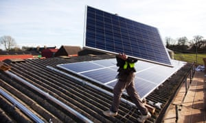 A workman intalls solar panels on a barn roof in Balcombe, West Sussex