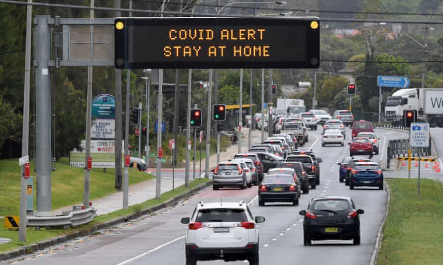 Cars queue for a drive-thru Covid-19 testing clinic on Pittwater road at Warriewood on Sydney's northern beaches