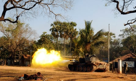 A Sri Lankan soldier stands near a tank as it fires a shell at Puthukkudiyirippu in March 2009